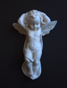 Front view of a very small white plaster cherub, artfully draped with its arms clasped above its garlanded head. On a dark grey background.