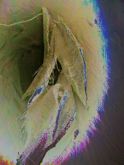 small scraps of muslin from the soft sculpture figures, photographed and edited in Photoshop, to produce an abstract image in black, and cream with purple blue giving the impression of a small black hole.