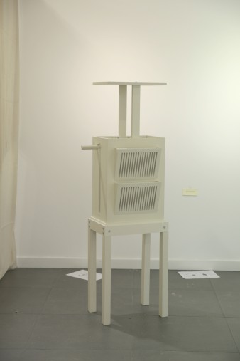 A photograph depicting a piece of adaptable furniture, which is painted off-white. It has a movable lid.