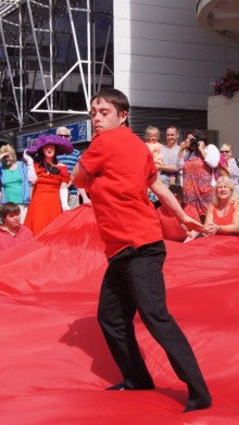 One of the RAWD performers dancing on a large red cloth in a Liverpool city square