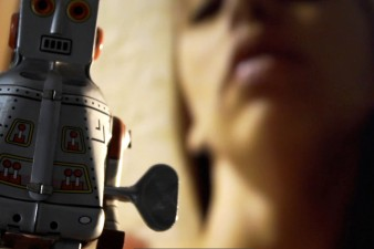 blurred image of the face of a young woman with a toy robot in the foreground