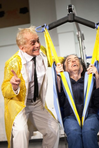 photo of actor David James in a long yellow jacket assisting actress liz carr into a hoist