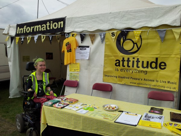 photo of a young wheelchair-user in a hi-viz jacket smiling at the camera next to an attitude is everything stall