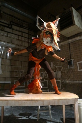 photo of a performer dressed as a large red fox standing on a table