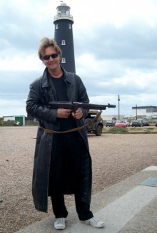 Charles Devus stands facing the camera with a smile. He holds a rifle., Dungeness Lighthouse is in the background
