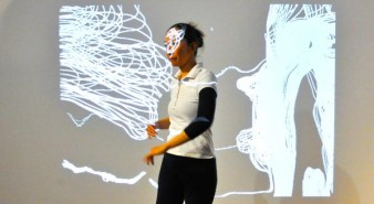 still image of dancer Chisato Minamimura set against the digital backdrop of visual images created through movement