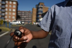 A photograph shows a child's hand holding a camera remote as he takes the picture. In the background is what appears to be a council estate.