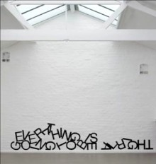 photo of the white brick wall of a gallery with a series of large black letters tumbling down near the bottom of the wall