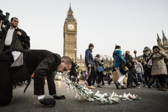 A photograph of Kris Canavan's performance piece Dredge. A man crawls across a road with flowers in his mouth, Big Ben can be seen in the background.