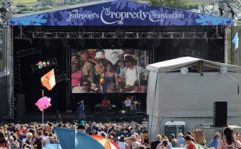 photo of a stage at the cropredy festival, with a large screen showing a seated performer playing guitar