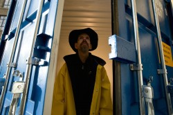 photo of Jez Colbourne wearing a yellow raincoat and a leather hat, standing in the open doors of a large shipping container