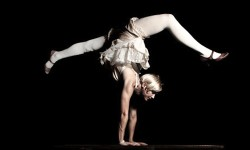 photo of female circus performer standing on her hands against a black background