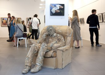 Cardboard sculpture or man sitting in chair in a gallery environment