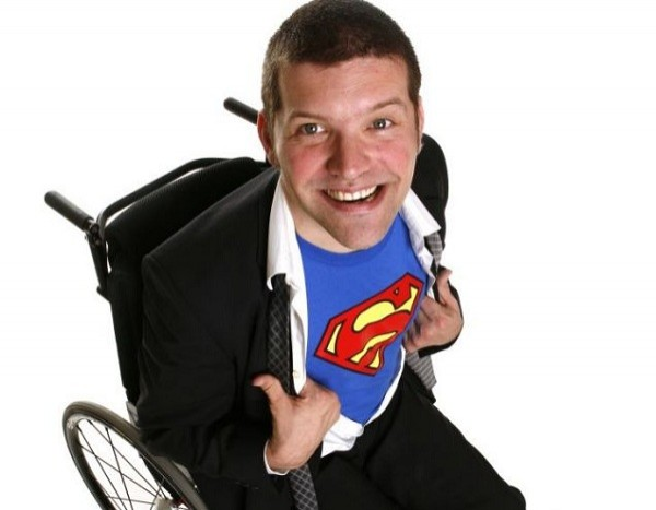 a man sitting in a wheelchair photographed from above smiling pulling open his shirt to show a Superman t-shirt