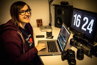 A photograph of multimedia artist Lisa Mattocks, she is sitting at her computer with video equipment on her desk.