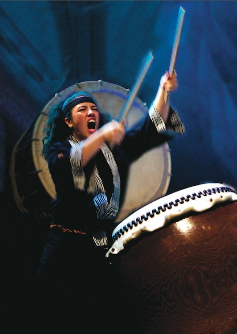 dynamic photo of woman drummer wielding a huge Japanese taiko drum