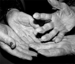 black and white photo of several elderly hands, palms up