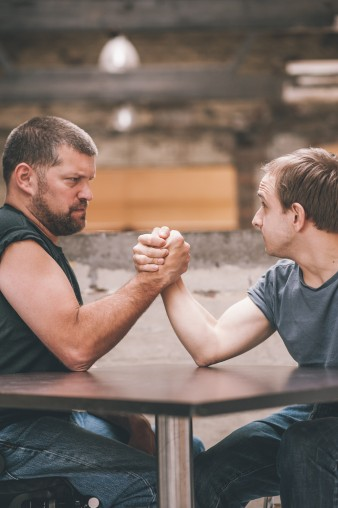 A promotional image from Bird of Paradise's production, Purposeless Movement's, showing two men arm wrestling, one is much bigger than the other.