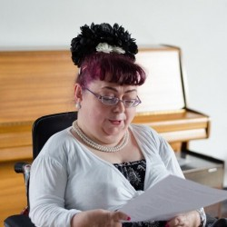 photo of performer Penny Pepper reading from a sheaf of paper, in front of a piano