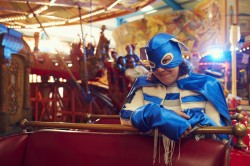 photo of Jessica Thom in blue superhero costume on a ride in a funfair