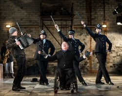 Garry Robson as JJ Peachum, King of the Beggars, leads a chorus of policemen in Graeae's touring production of The Threepenny Opera