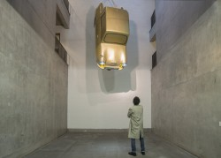 A photograph of Tony Heaton's installation Gold Lamé a golden invacar suspended from the ceiling