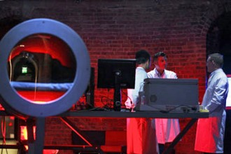 photo of three men in white lab coats standing near a table with computer screens and a large round sculptural object in a room lit with red light