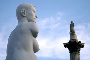 A white marble-looking statue of a nude young white woman without arms looks over towards Nelson