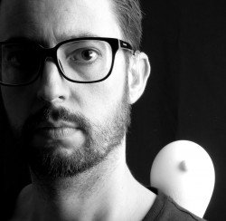 black and white photo of artist chris sacre with condom sculpture peering over his shoulder