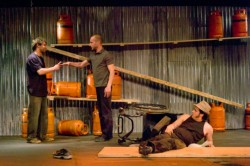 three male circus performers stand by a series of planks and red gas canisters