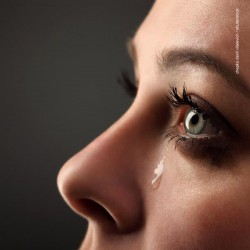 poster image of the side of a young woman's face with a tear rolling down her cheek