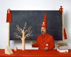 photo of the artist in a red suit in front of a white board