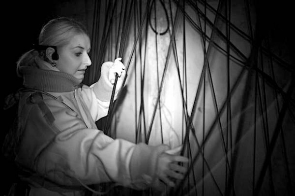 black and white photo of a woman grappling with webbing in the dark