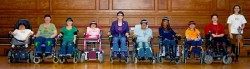 photo of a line of female wheelchair-users dressed in colourful costumes