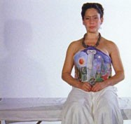 Isolte Avila playing Frida Kahlo, sits on a surgical couch. She is wearing the plaster corset painted with the image of a sun and moon, separated by a classical column.