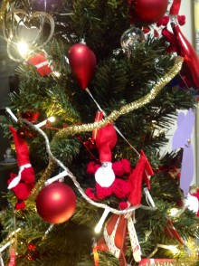 Close up of green Christmas tree with typically ScandiBrit red and white decorations.