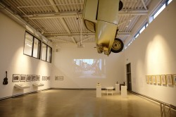 Installation shot from Art, Life, Activism, featuring Tony Heaton's Gold Lame hanging from the ceiling, Aaron Williamson's sculptures in the foreground, Noëmi Lakmaier's video projected on the back wall and Boobby Baker's drawings on the right.