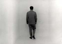 black and white photo of the back of a man in a suit in a white room