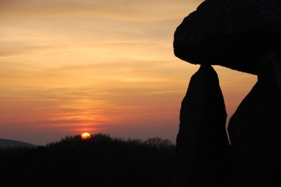 photo of sunset over a prehistoric burial chamber