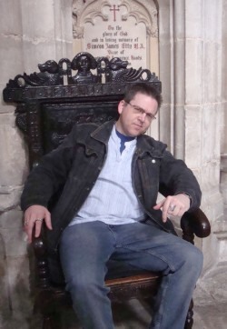 Fred photographed on a wooden throne in Winchester Cathedral