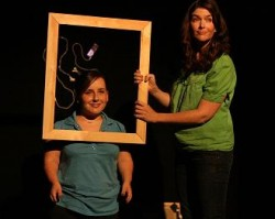 photo shows two women on stage with one of them holding a picture frame, which frames the face of the other Photo by Jon Pratty/dao