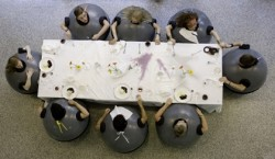 photo of a group of six people around a dinner table, dressed in grey 'weeble'