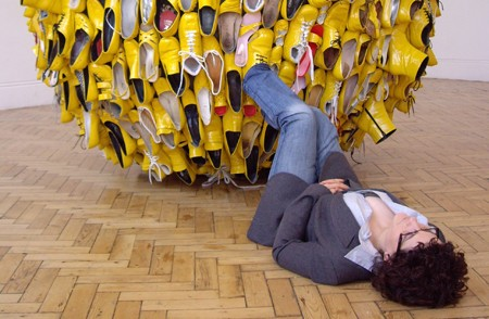 photograph of artist Noemi Lakmaier dressed in a suit, lying on the floor of a gallery with her feet attached to a very large ball of yellow shoes