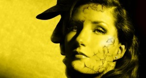A woman's face looking out against a yellow background and the silhouette of a person wearing a hat.