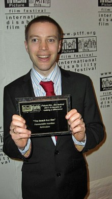Stephen dressed in a suit with an award for 'The beach hut film'