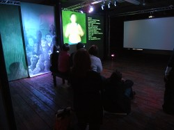 photo shows a darkened room with images projected onto the walls. In the foreground people are sitting and watching the images