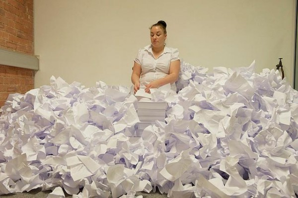 a woman in a white dress stands waist deep in a large pile of crumpled white paper