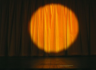 Sonja Zelic - An invitation to speak it features a closed theatre curtain with a spotlight on it