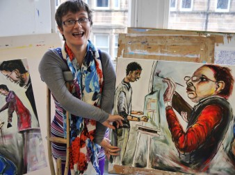 A photograph of the artist Tanya Raabe-Webber in her studio with a selection of portraits for Summit Portrayed