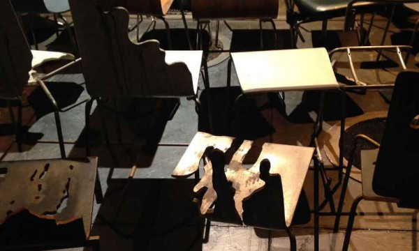 photo of a group of utilitarian chairs with a shadow of a couple emblazoned on one of the wooden seat panels